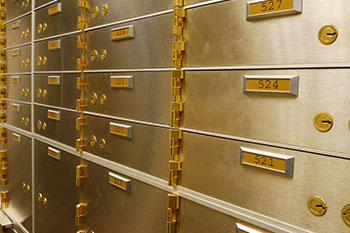 Metal safe deposit boxes with brass numbers and hinges.
