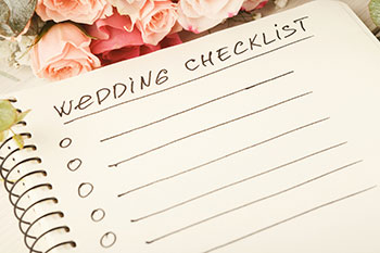 A notebook with wedding checklist written on it.